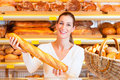 Female baker in her bakery with baguette Stock Images