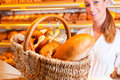 Female baker in her bakery or saleswoman with fresh pastries and products Royalty Free Stock Photos