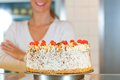 Female baker or pastry chef with torte Stock Image