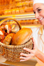 Female baker selling bread by basket in bakery or saleswoman her fresh pastries and products Stock Photo