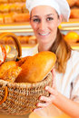 Female baker selling bread by basket in bakery or saleswoman her fresh pastries and products Stock Photos