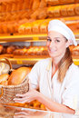 Female baker selling bread in her bakery or saleswoman with fresh pastries and products Royalty Free Stock Photos