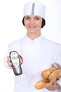 Female baker showing phone her Stock Image