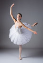 Female ballet dancer beautiful on a grey background ballerina is wearing a white tutu and pointe shoes Royalty Free Stock Photo