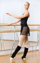 Female ballet dancer dancing near barre in dancing hall wearing leotard and warmers dances and mirrors Royalty Free Stock Image