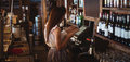Female bar tender looking at menu Royalty Free Stock Photo