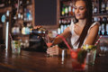 Female bartender pouring cocktail drink in the glass Royalty Free Stock Photo