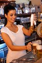 Female bartender tapping beer in bar portrait of attractive smiling Stock Image
