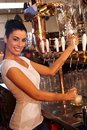Female bartender tapping draught beer in pub portrait of attractive mug of smiling Royalty Free Stock Photos