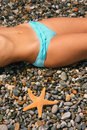 Female beautiful body with on stony beach Royalty Free Stock Images