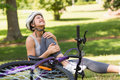 Female bicyclist with hurt leg sitting in park young on grass the Royalty Free Stock Photos