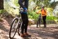 Female biker walking with mountain bike on dirt track Royalty Free Stock Photo