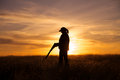 A female bird hunter silhoutted against a dramatic sunset with shotgun Stock Image