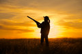 A female bird hunter silhoutted against a dramatic sunset with shotgun Stock Photos