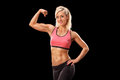 Female bodybuilder showing her bicep on black background Royalty Free Stock Image