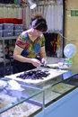 Female boss finishing black gem amulet in liwan jade jewelry market Royalty Free Stock Photo