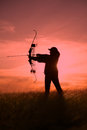 A female bowhunter hunter silhoutted against a dramatic sunset with recurve bow Stock Image