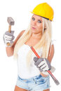 Female building labor sexy young blonde girl working as with a yellow helmet hammer and chisel or gouge Royalty Free Stock Image