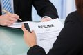 Female candidate holding resume at desk Royalty Free Stock Photo
