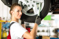 Female car mechanic working on jacked auto Royalty Free Stock Photo