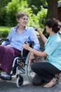 Female caregiver talking with handicapped woman on wheelchair young senior women Royalty Free Stock Photo