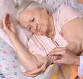 Female caretaker checking pulse of old woman at nursing home Royalty Free Stock Image