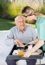 Female caretaker serving breakfast to senior man men at nursing home Stock Photography