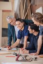 Female carpenter working with colleagues in portrait of confident at table workshop Stock Photos
