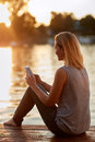 Female with cellphone relaxing near water Royalty Free Stock Photo