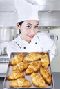 Female chef holding croissants kitchen Royalty Free Stock Photos