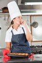 Female chef licking finger happy while holding tray breads in restaurant kitchen Royalty Free Stock Photography