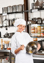 Female chef mixing egg with wire whisk in bowl portrait of mid adult at commercial kitchen Stock Images