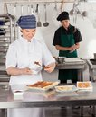 Female chef preparing sweet food happy with colleague in background Royalty Free Stock Photography