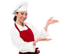 Female chef presenting something pretty cook greeting the customers and directing them the way Royalty Free Stock Photography