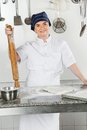 Female chef with rolling pin by kitchen counter portrait of standing industrial Stock Photo