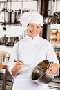 Female chef with wire whisk and mixing bowl portrait of happy at commercial kitchen Royalty Free Stock Photography