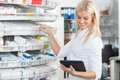Female chemist standing in pharmacy drugstore with tablet pc Stock Photo