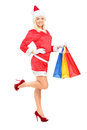 Female in christmas costume holding shopping bags Stock Photo