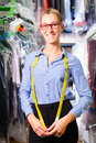 Female cleaner in laundry shop or dry cleaning textile next to clean clothes garment bags Royalty Free Stock Photos