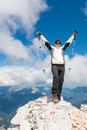 Female climber celebrating a successful ascend standing on top of mountain and her Royalty Free Stock Photo