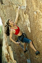 Female climber clinging to a cliff. Stock Photos