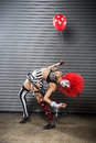 Female clown bent over backwards cute woman bending while holding a red balloon Stock Photo