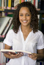 Female college student reading in a library Royalty Free Stock Photo