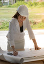 Female construction site engineer/Young engineers are checking the plan. Royalty Free Stock Photo