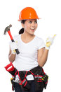 Female construction worker in action a woman wearing a tool belt full of a variety of useful tools and pointing up Stock Photos