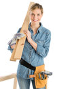 Female Construction Worker Carrying Wooden Plank On Shoulder Royalty Free Stock Photo