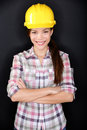 Female construction worker or engineer portrait home owner in renovations posing on black background young woman wearing yellow Royalty Free Stock Photos