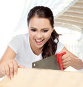 Female construction worker with saw portrait of pretty housewife doing some contruction work Stock Photos