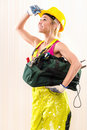 Female construction worker with tool bag indoors Royalty Free Stock Photos