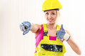 Female construction worker woman in coverall and hard hat showing thumbs up indoors Stock Image